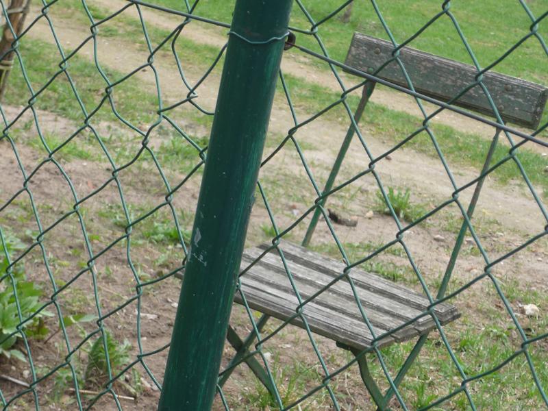 Stuhl hinter Zaun